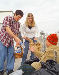 Young Man and Woman Giving Food and Water to Homeless Man